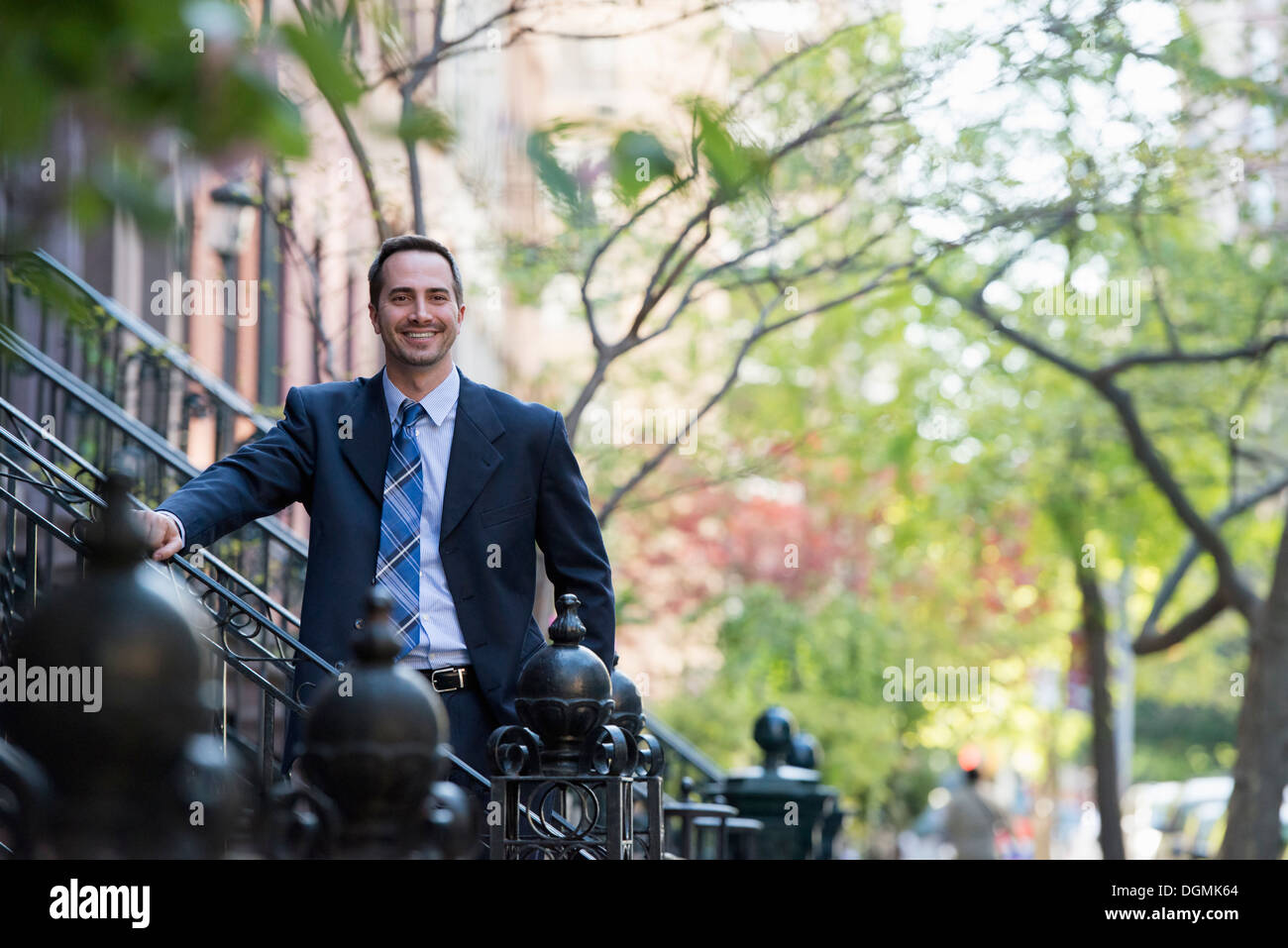 A man in a business suit standing on the steps on a street. - Stock Image