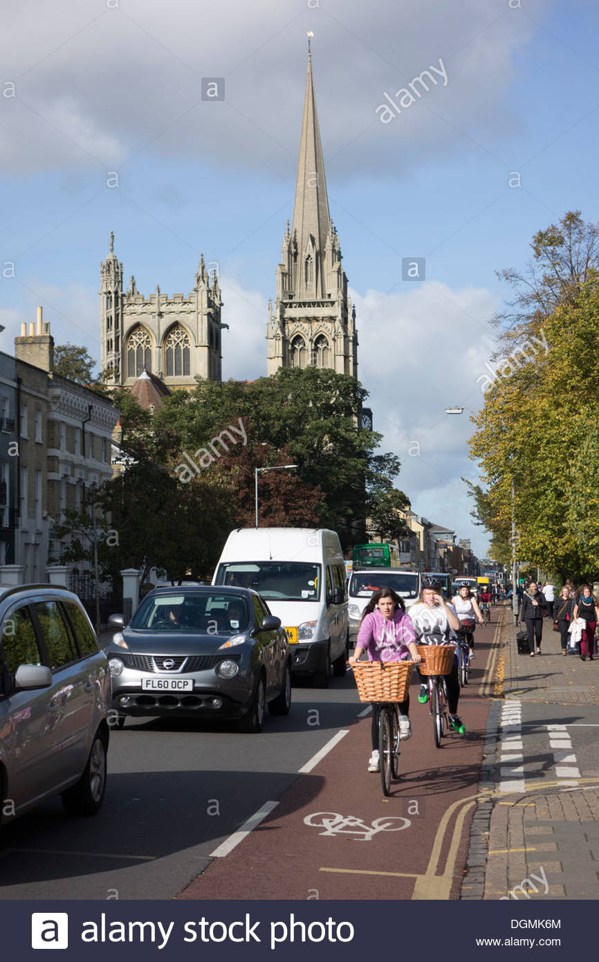 Cyclists use the cycle lane on a busy Hills Road in Cambridge, with the Catholic Church in the distance. - Stock Image