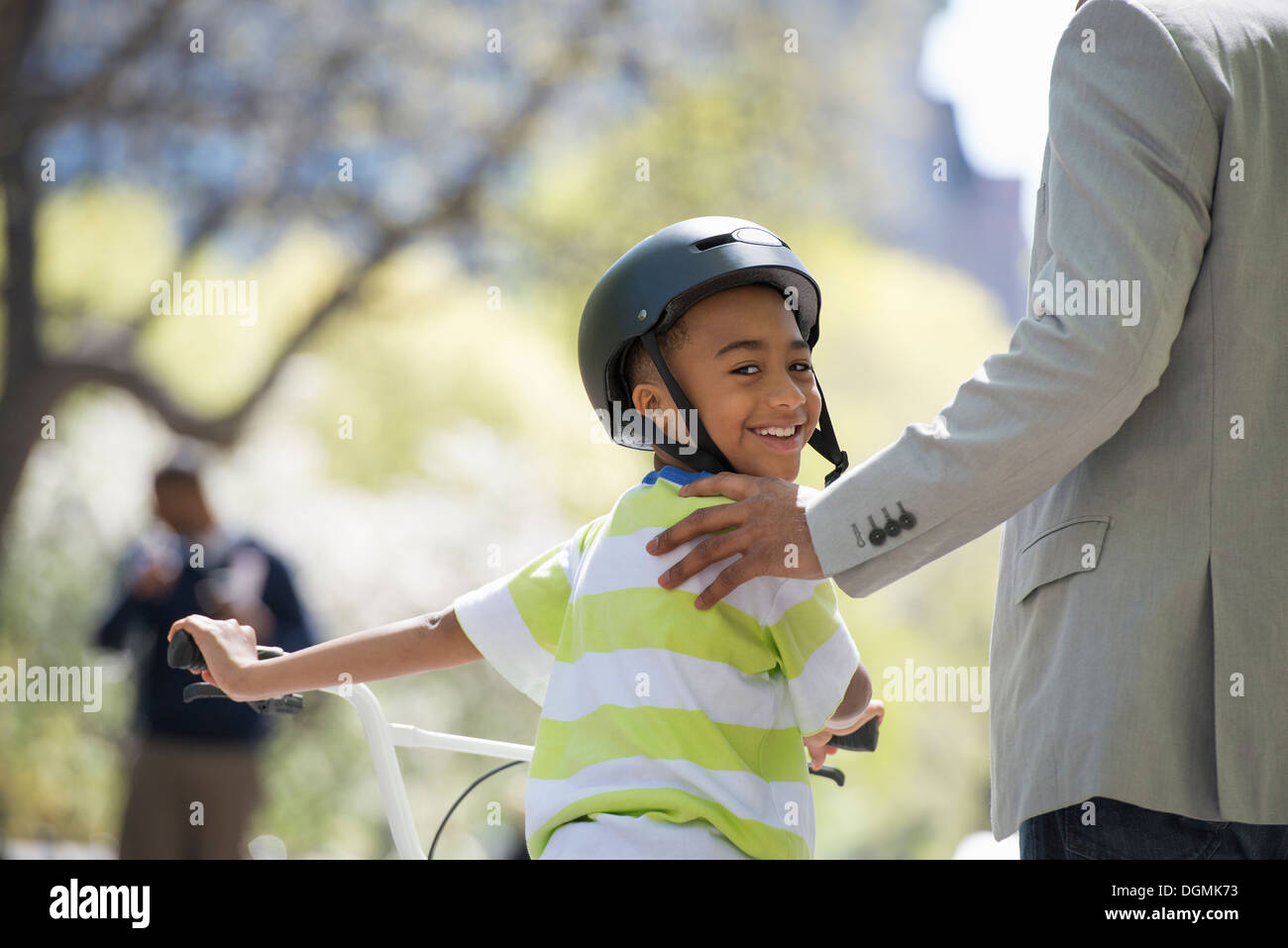 Bicycling and having fun. A father and son side by side. - Stock Image