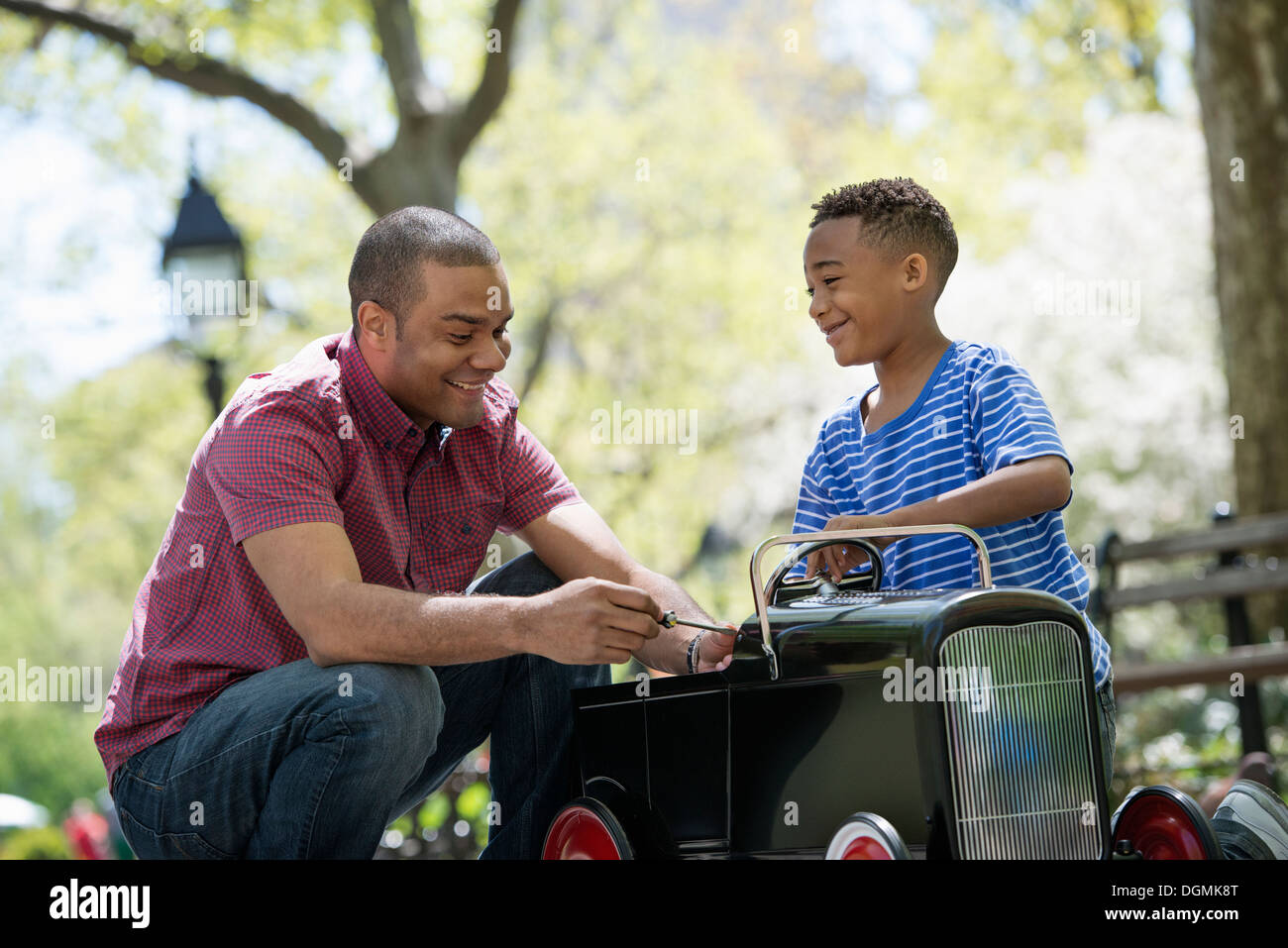 A boy riding an old fashioned toy peddle car. - Stock Image