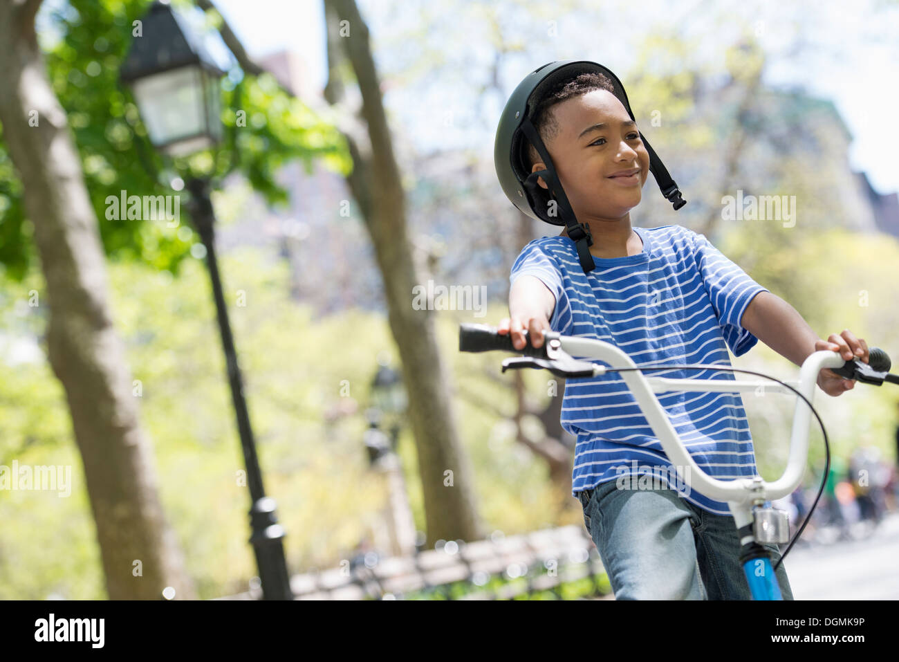 A family in the park on a sunny day. Bicycling and having fun. - Stock Image