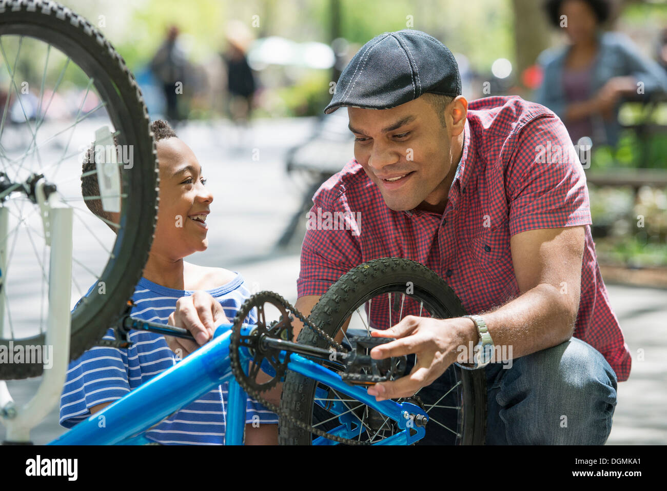 A family in the park on a sunny day. A father and son repairing a bicycle. - Stock Image