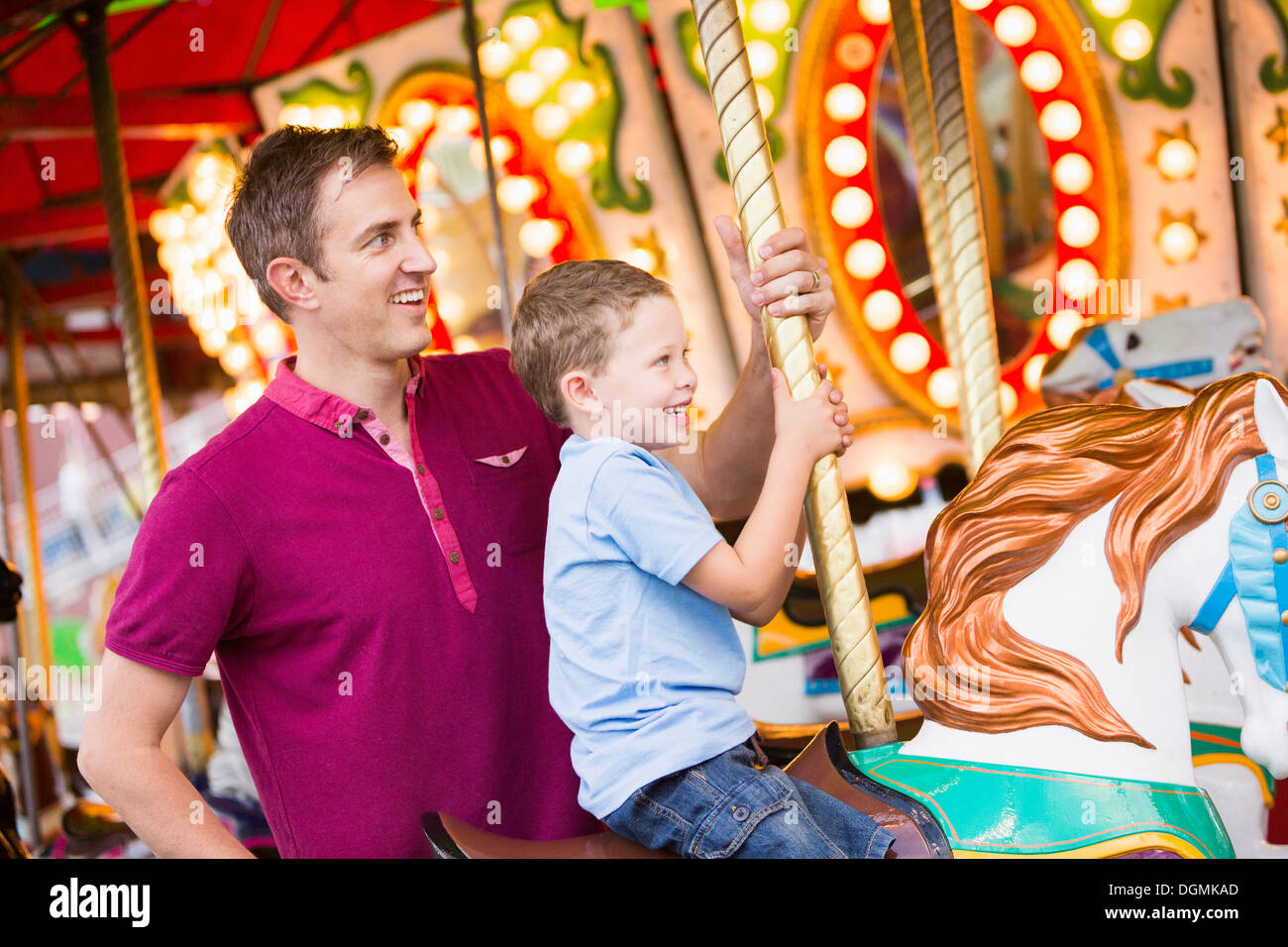 USA, Utah, Salt Lake City, Father and son (4-5) on carousel in amusement park - Stock Image