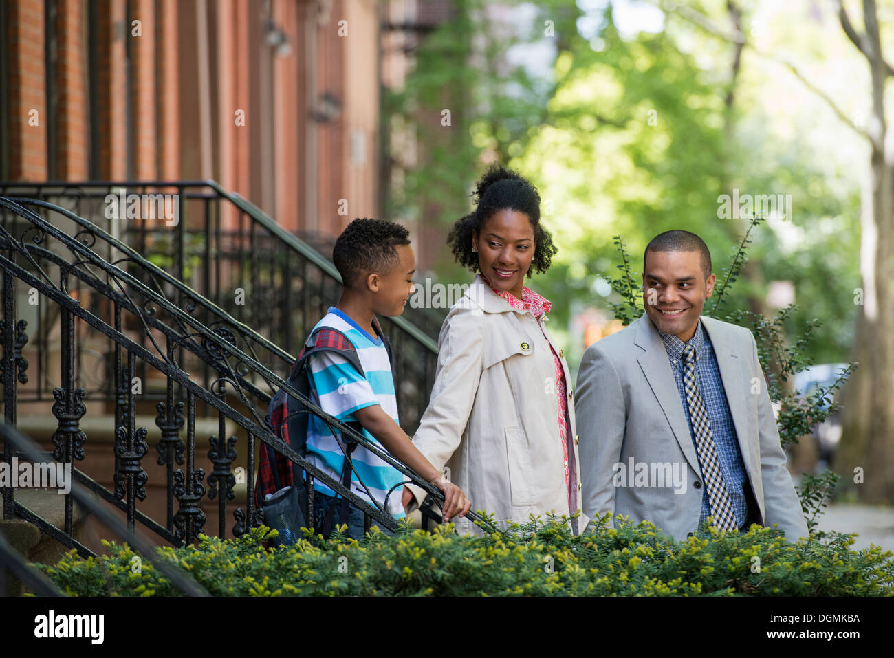 A family outdoors in the city. Two parents and a young boy walking together. - Stock Image