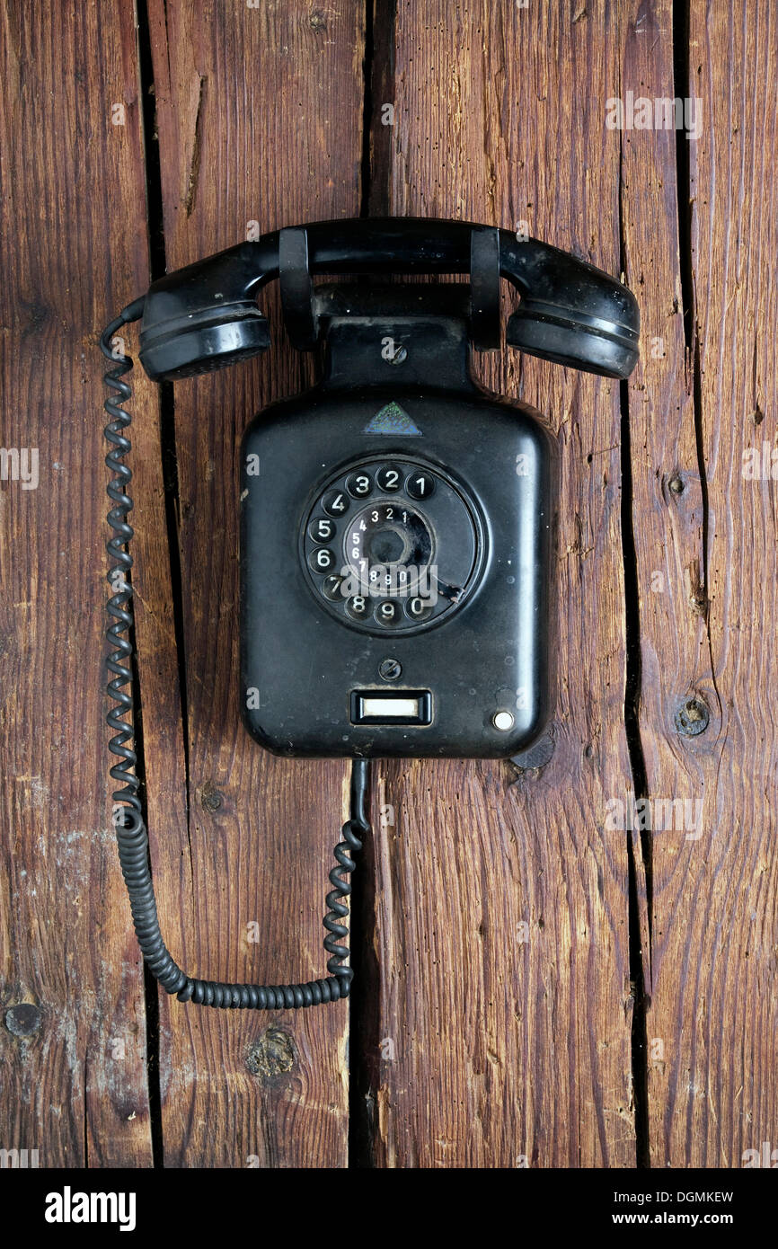 Old Bakelite wall telephone from 1950, hanging on a rustic wooden wall - Stock Image