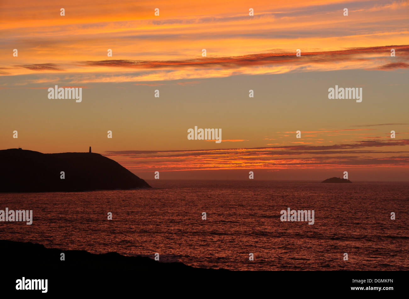 North Cornwall - sunset over silhouette Stepper Point - orange red and blue cloudscape  over crimson sea - twilight - Stock Image