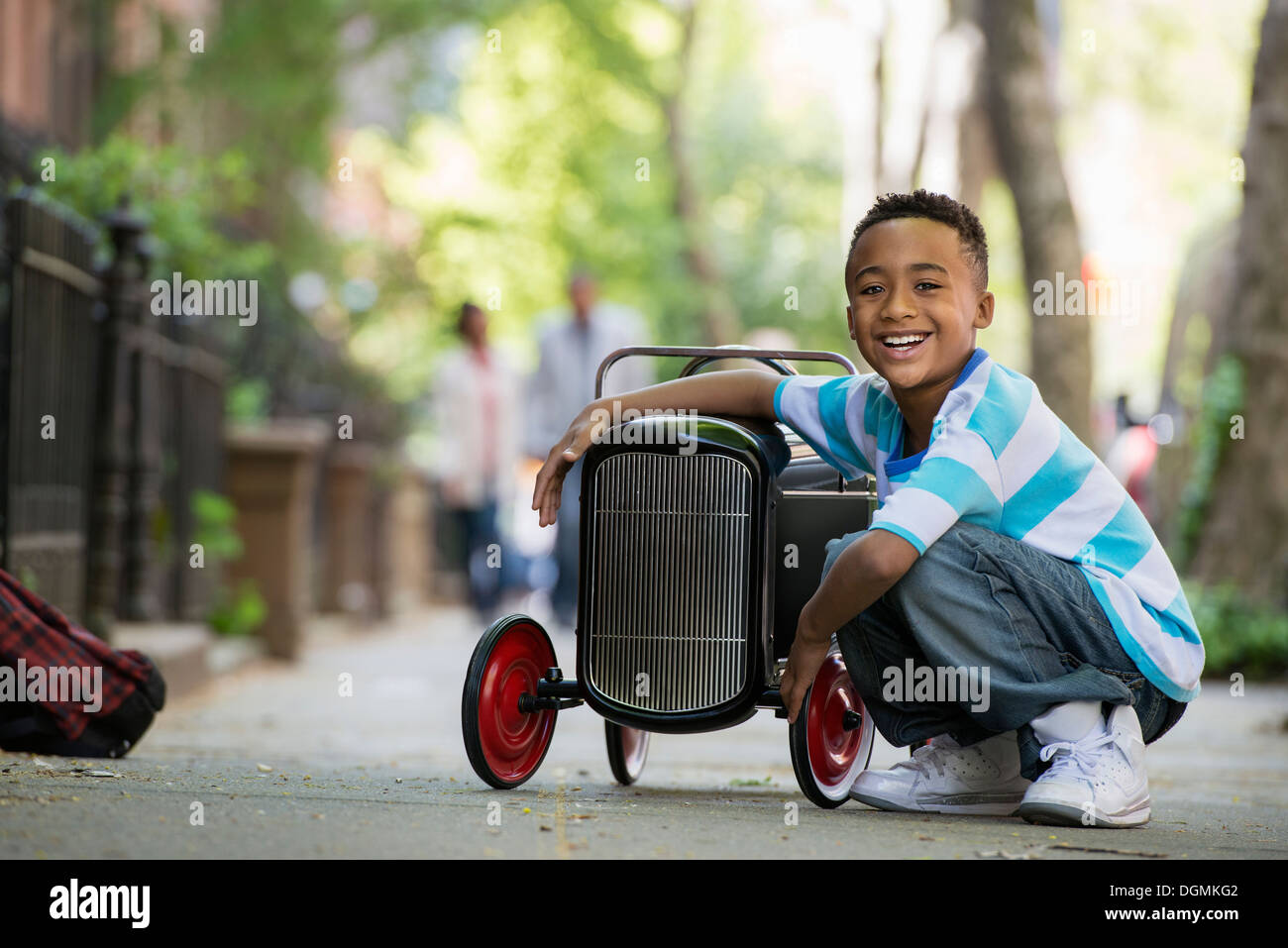 A young boy playing with a old fashioned toy car on wheels on a city street. - Stock Image