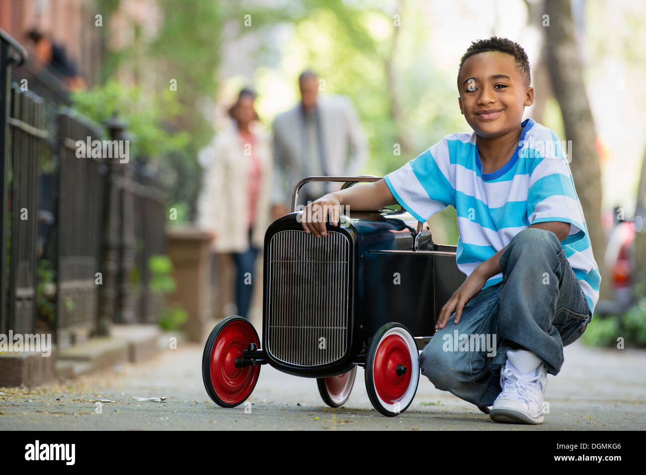 A young boy playing with a old fashioned toy car on wheels on a city street. A couple looking on. - Stock Image