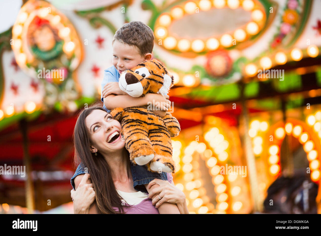 USA, Utah, Salt Lake City, Mother giving her son (4-5) piggyback ride in amusement park - Stock Image