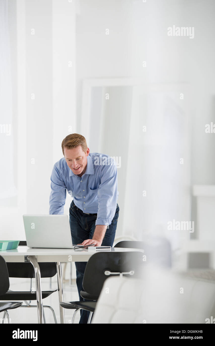 Business. A man standing over a desk, leaning down to use a laptop computer. - Stock Image
