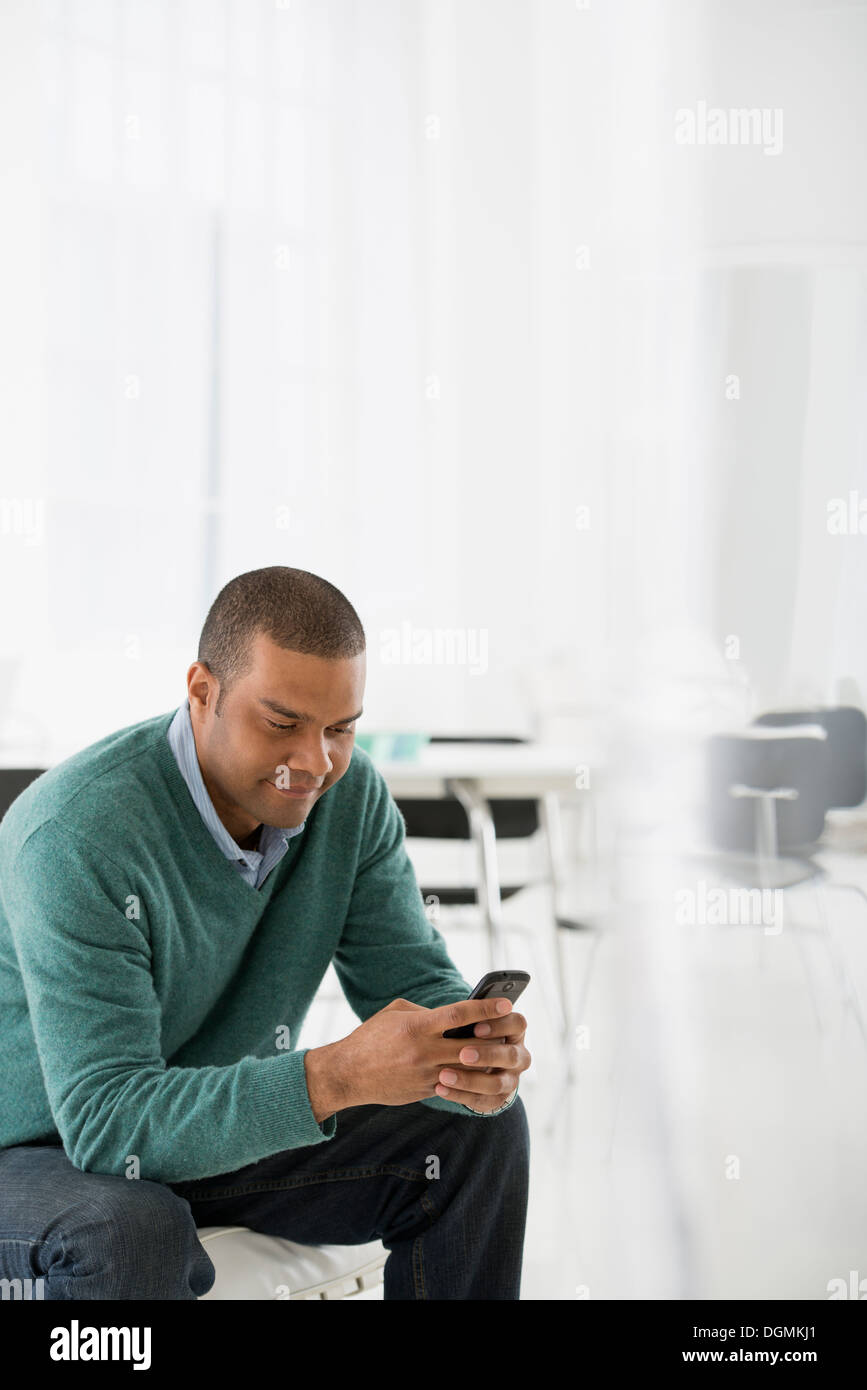 Business. A man seated, checking his smart phone for messages and texting. - Stock Image