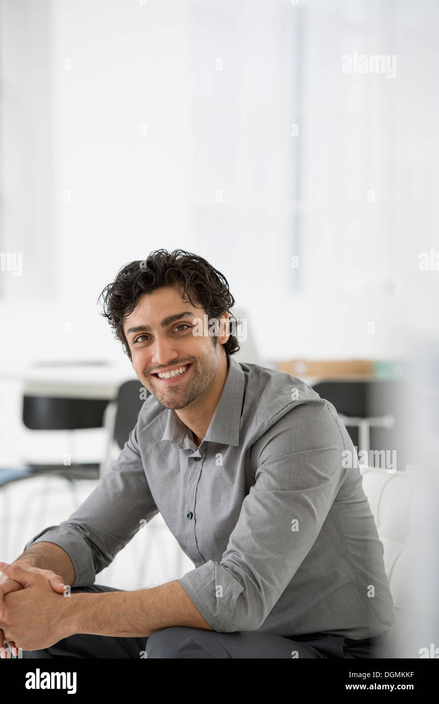 Business. A man seated with his hands clasped in a relaxed pose. Smiling and leaning forwards. - Stock Image