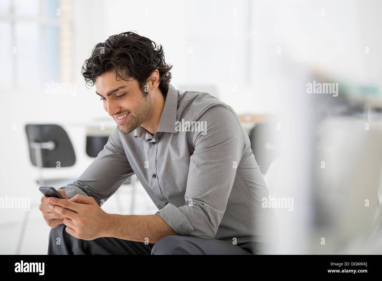 Business. A man seated looking at the screen on his smart phone. - Stock Image