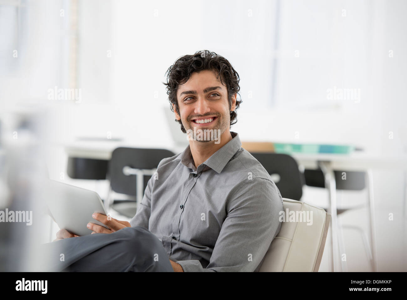 Business. A man seated smiling and holding a digital tablet. - Stock Image