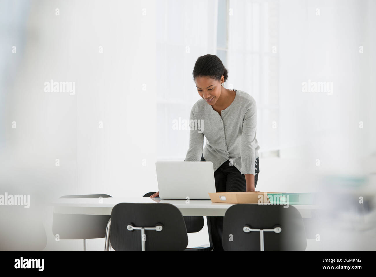 Business. A woman leaning over a desk using a laptop computer. - Stock Image