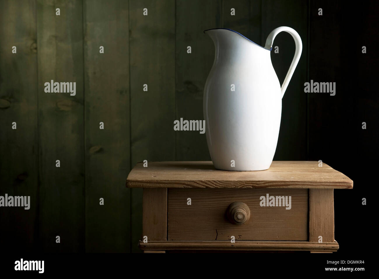 Old enamel jug on a small chest of drawers - Stock Image