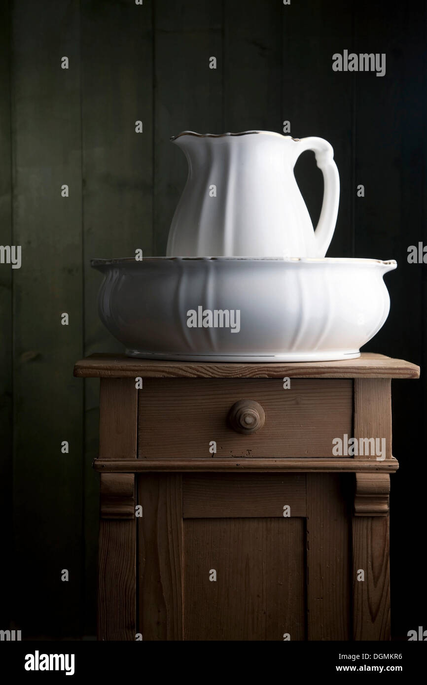 Antique porcelain basin on a small chest of drawers - Stock Image