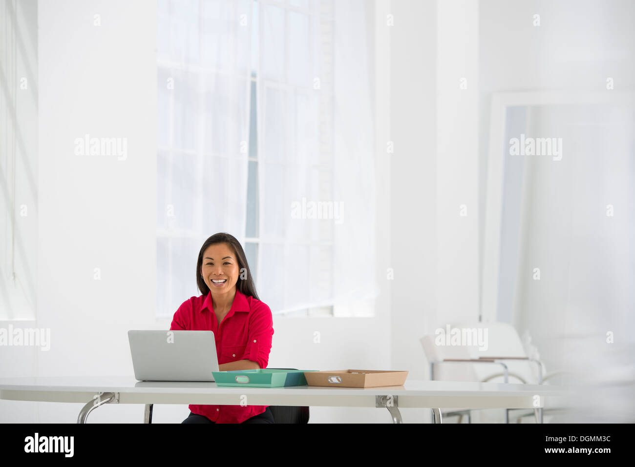 Asian businesswoman seated at desk using a laptop. - Stock Image