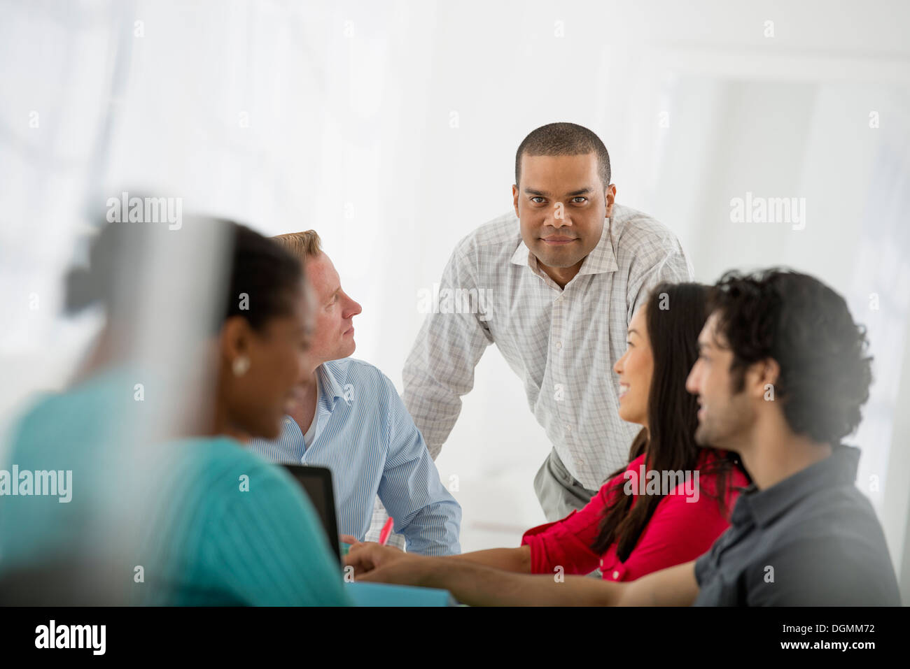 A multi ethnic group of people around a table, men and women. Teamwork. Meeting. - Stock Image