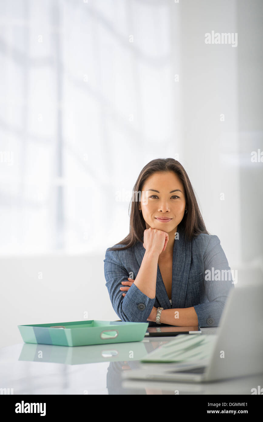 Business. A woman sitting relaxing, with her chin on her hand. - Stock Image