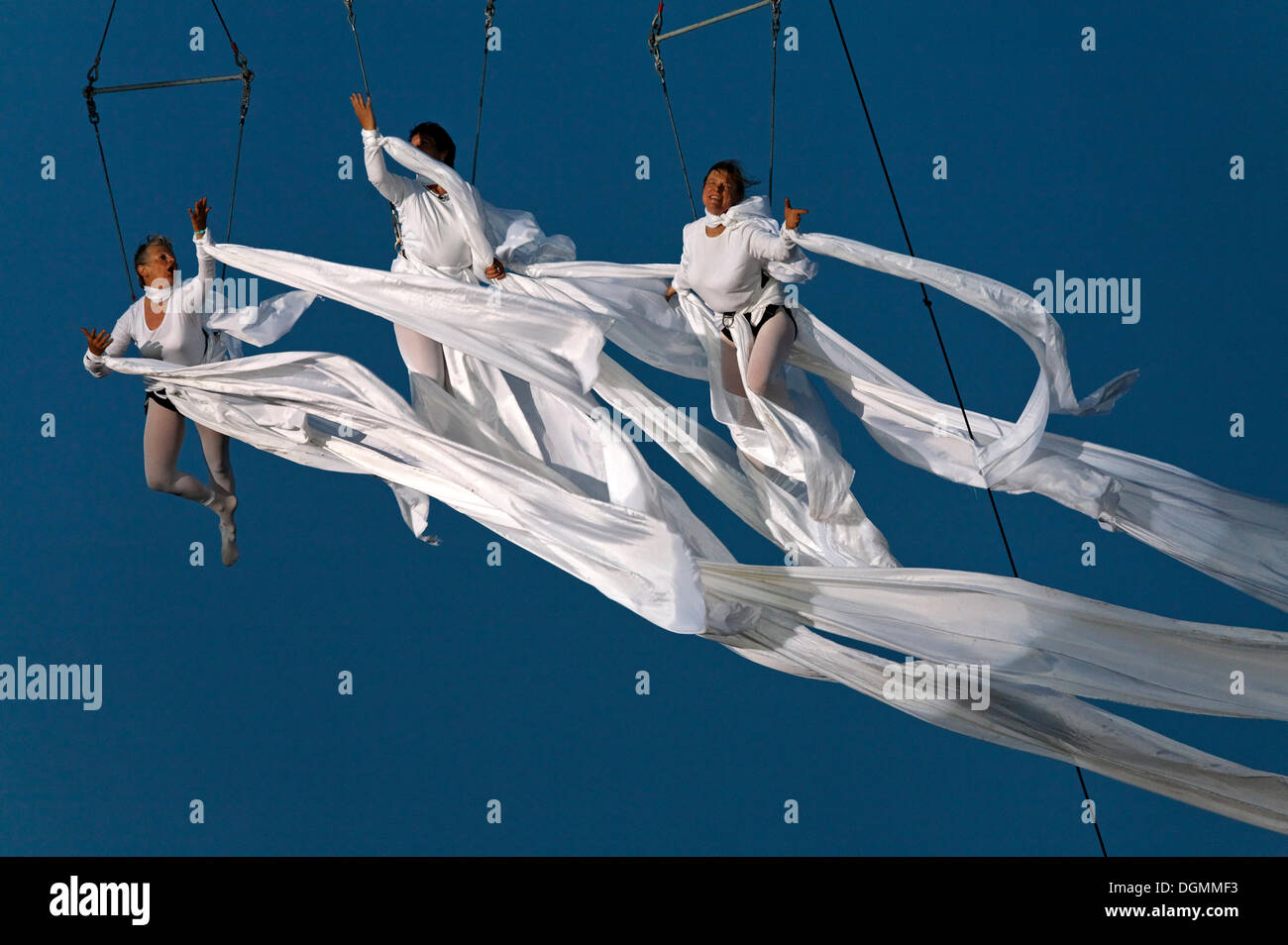 Three artistes hover in the air, wrapped in fluttering veils, Global Rheingold, open-air theater by La Fura dels Baus - Stock Image