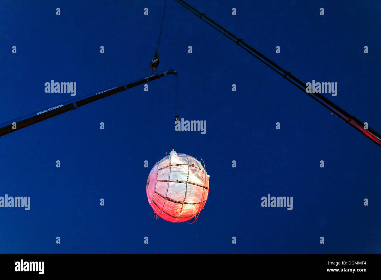Illuminated balloon hanging from ropes in the air, globe, Global Rheingold, open-air theater by La Fura dels Baus - Stock Image