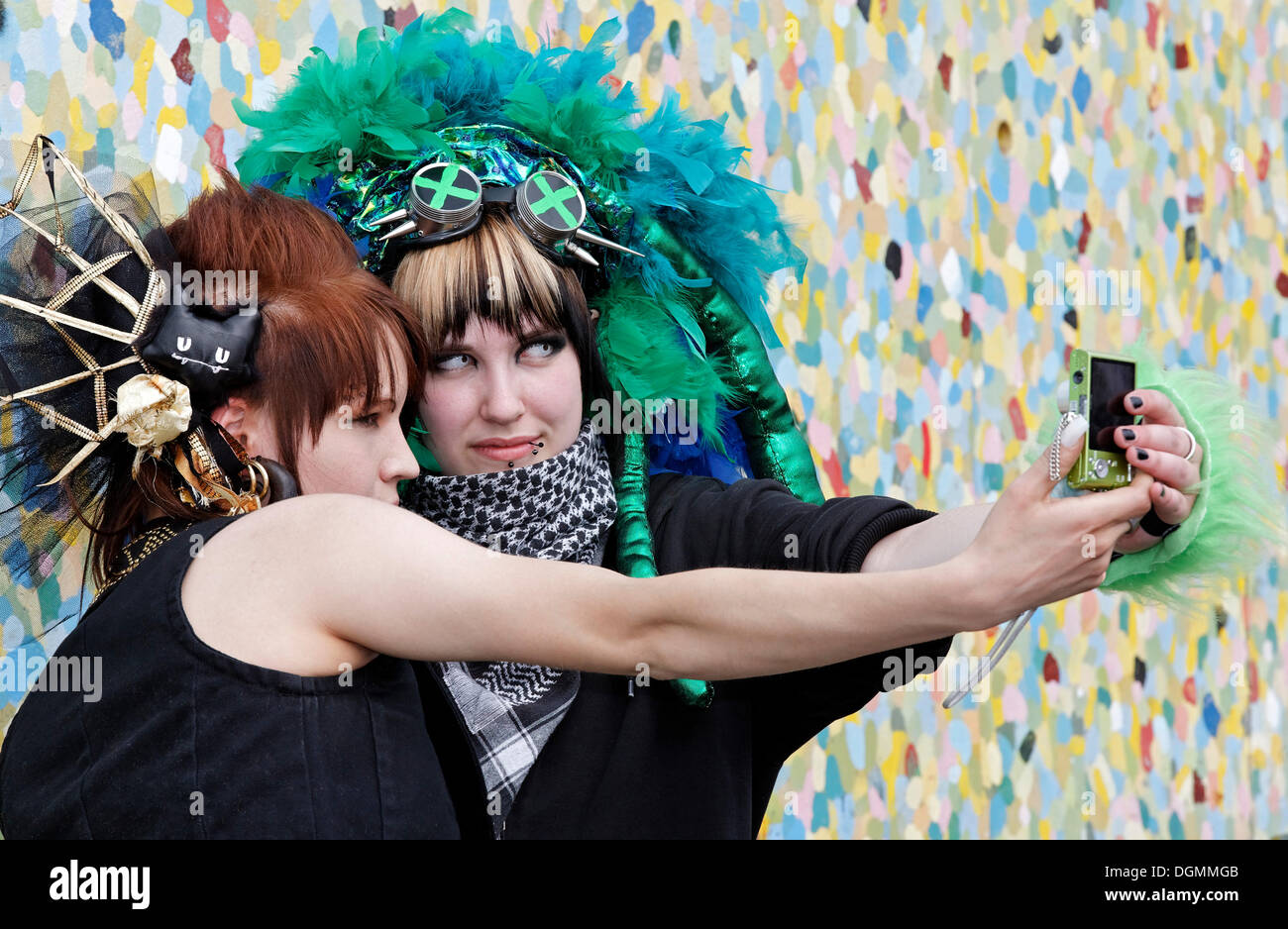 Two young women with bizarre headdress photographing themselves with their mobile phone, imaginative costumes, cosplayers - Stock Image