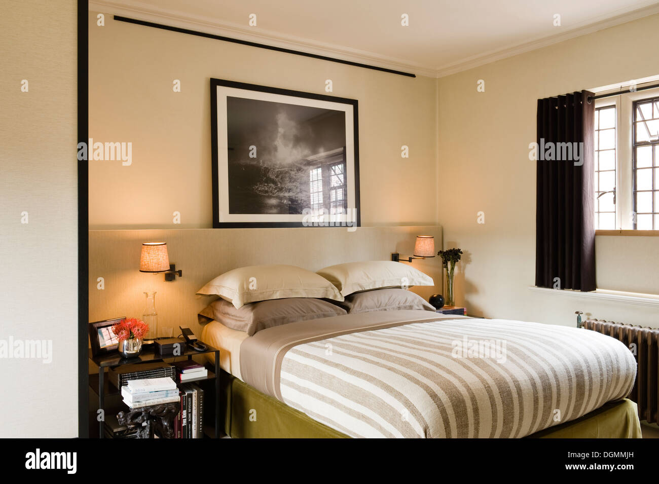 Large framed photograph by Dodo Jin Ming above bed with striped ...