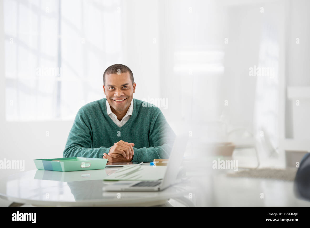 Business. A man sitting with his hands clasped behind a desk. - Stock Image