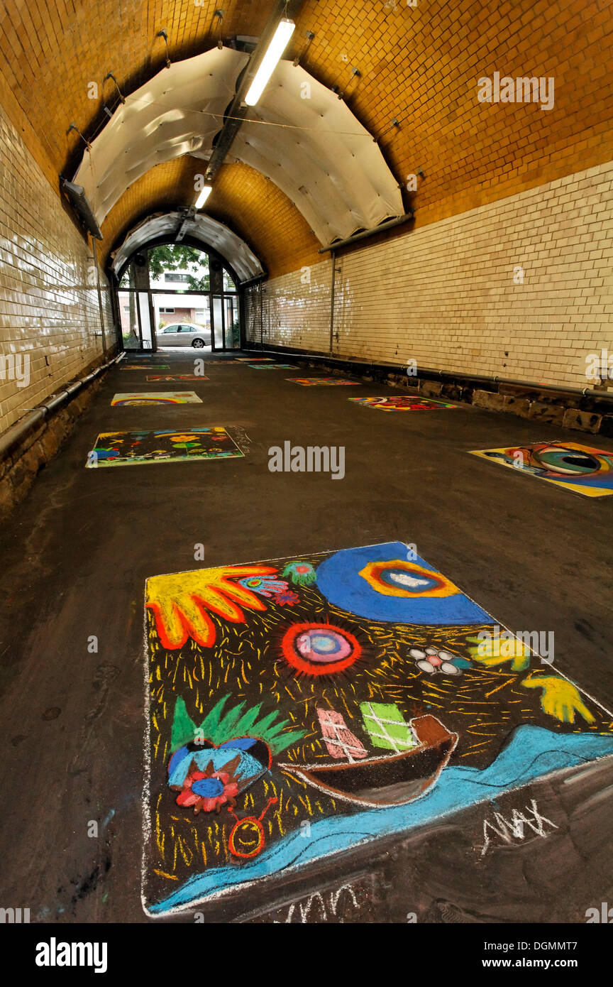 Pedestrian tunnel with chalk drawings on the ground, painted by children, disused Suedbahnhof railway station, Krefeld Stock Photo