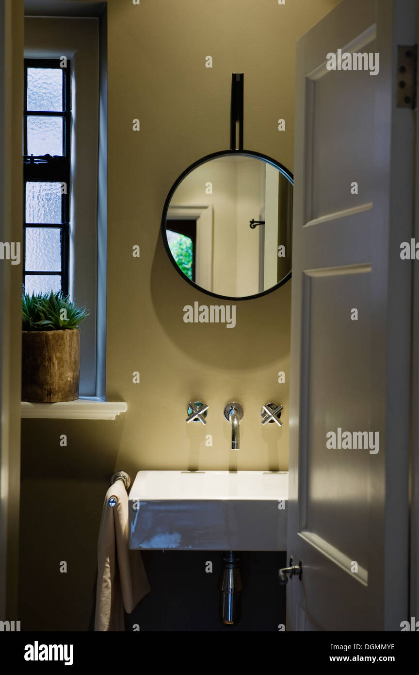 Bathroom with 1930's style sink and chrome taps. Rui Ribeiro designed lacquer-framed mirror - Stock Image