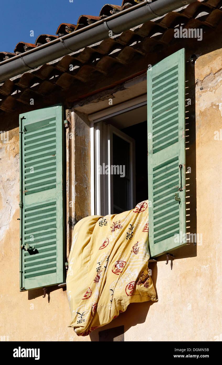 Duvet hanging out of a window, historic district of Bormes-les-Mimosas, Provence-Alpes-Côte d'Azur region, France, Europe - Stock Image