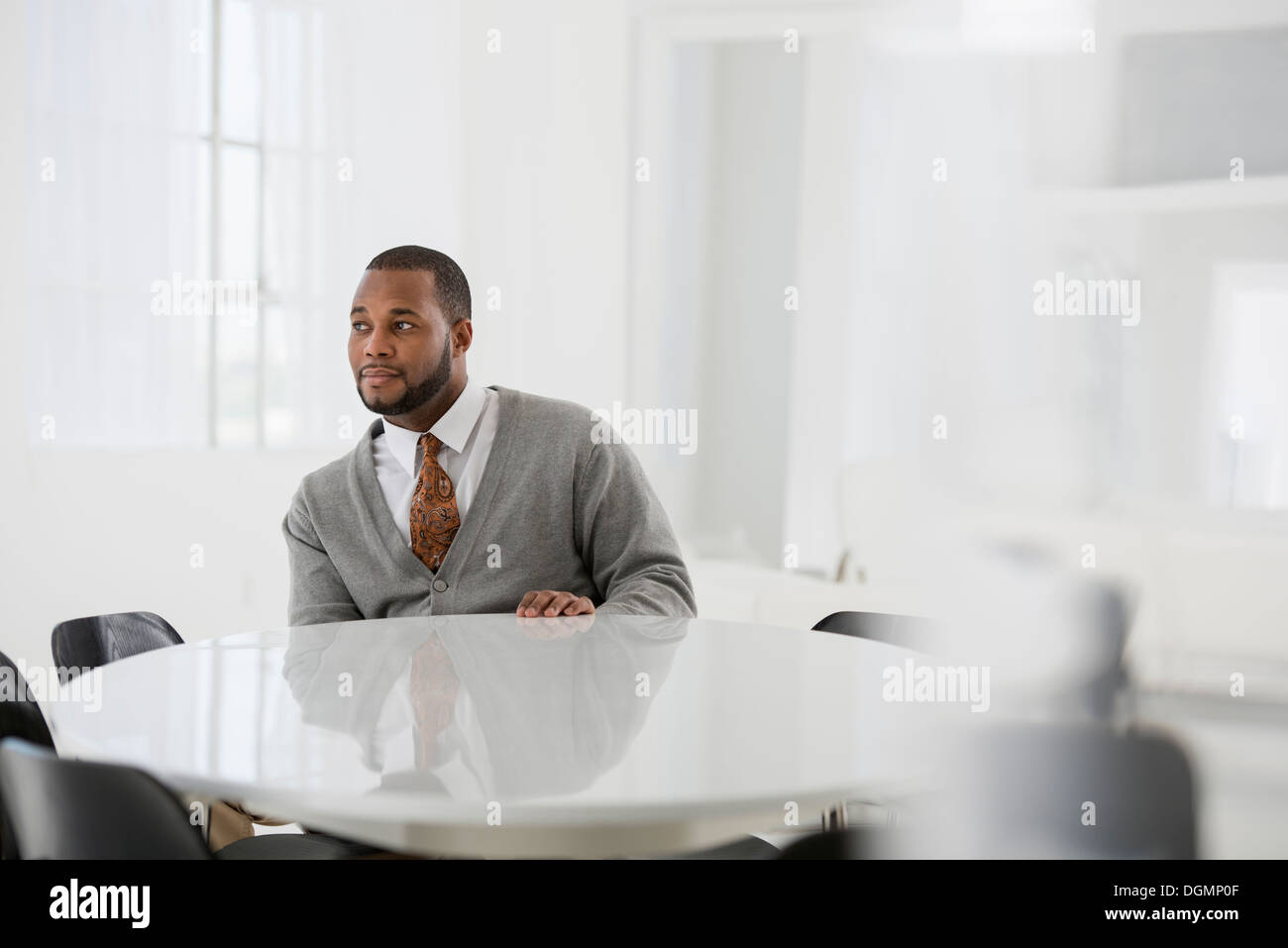 Office interior. A man in a business suit at a table seated at a table. - Stock Image