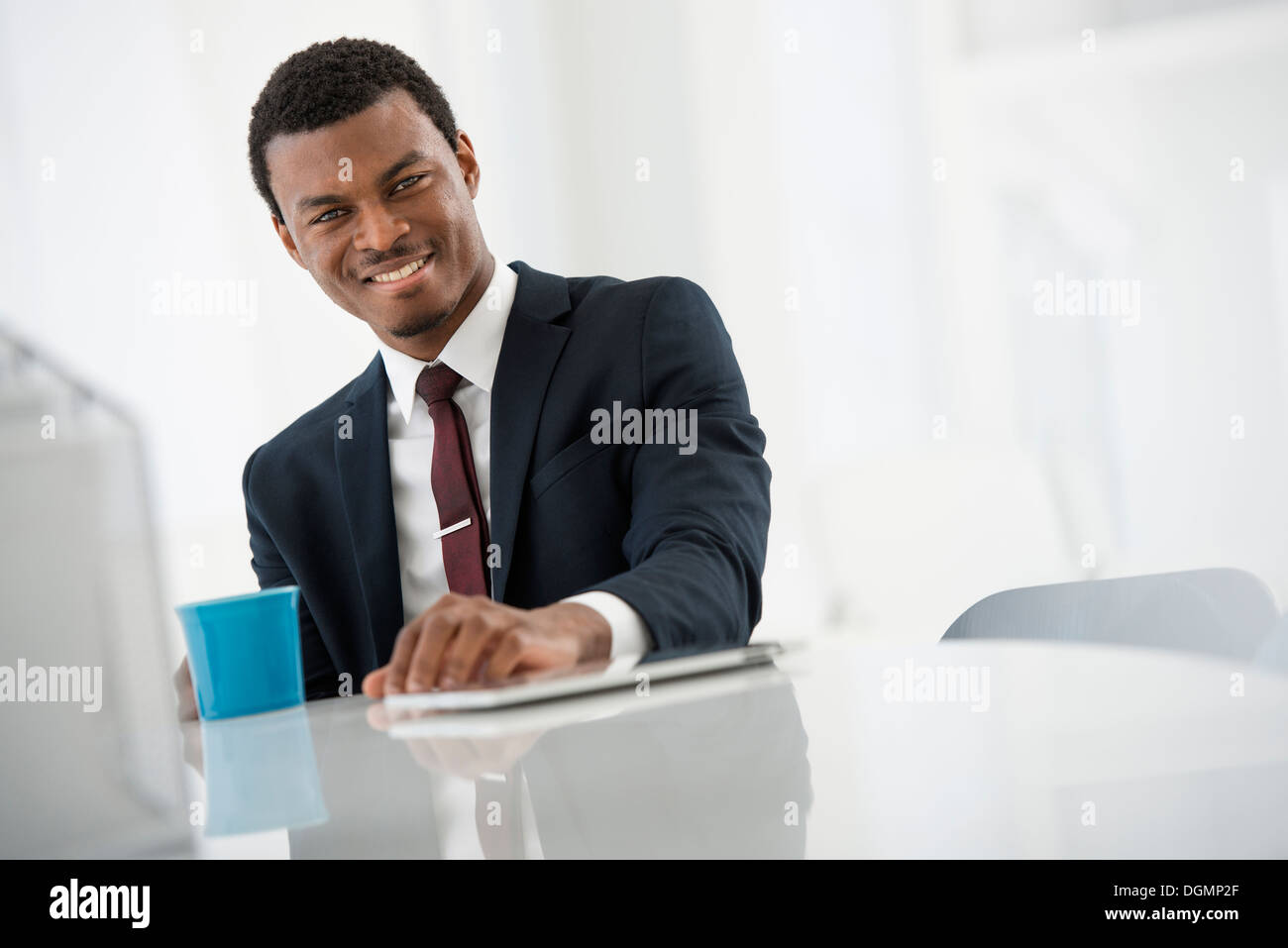 Office interior. A man in a suit with a cup of coffee. A digital tablet on the table. - Stock Image