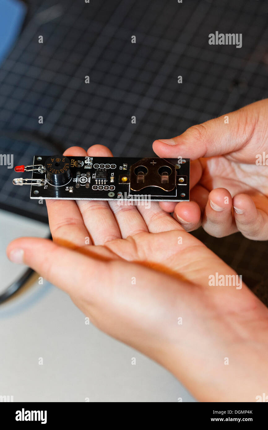Child's hands holding an electronic component with light emitting diodes, IdeenPark 2012, technology and education summit - Stock Image