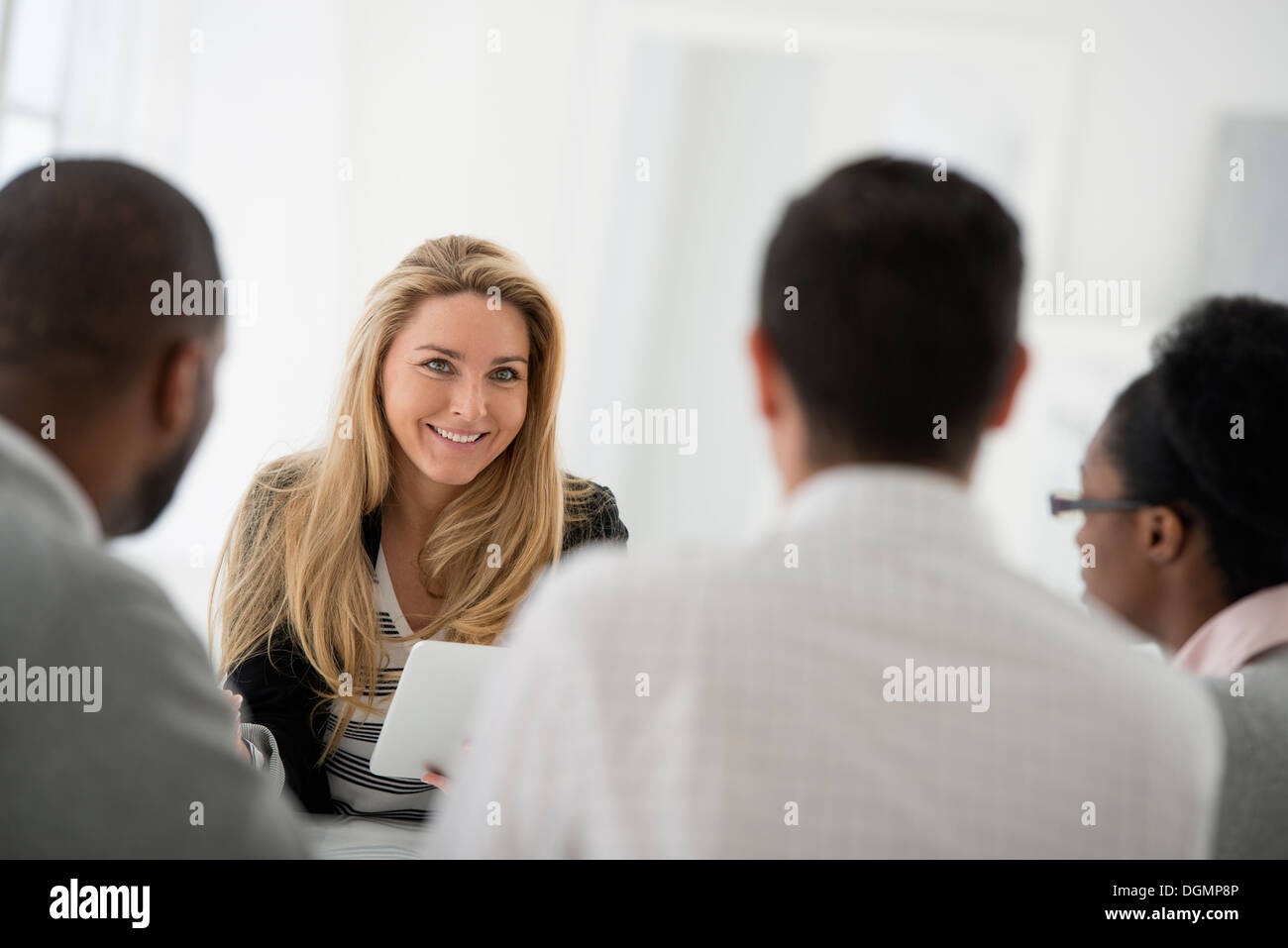 Office interior. A group of four people, two men and two women, seated around a table. Business meeting. - Stock Image