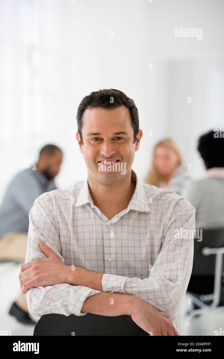 Office interior. A man seated separately from a group of people seated around a table. A business meeting. - Stock Image