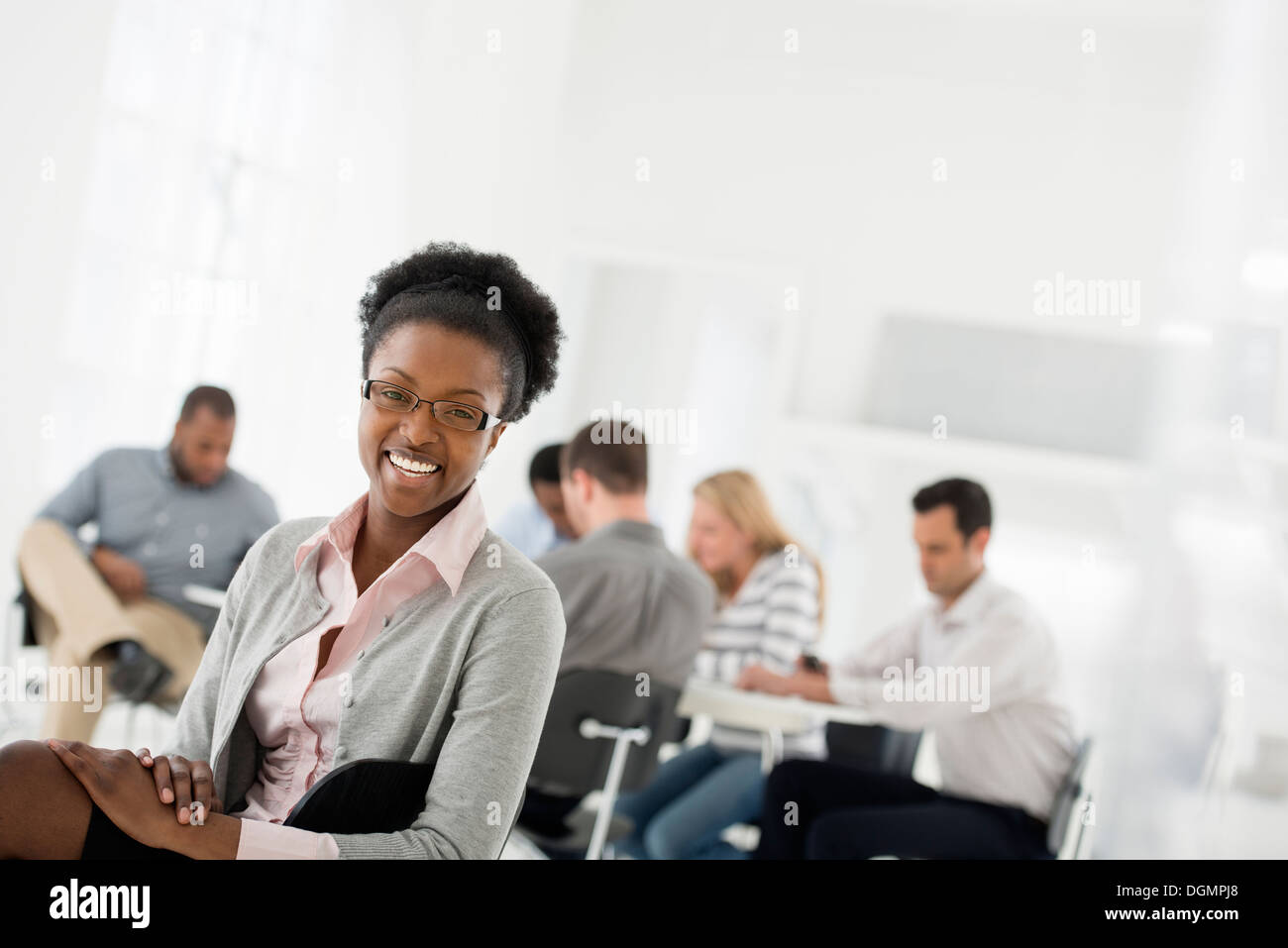 Office interior. A group of people meeting. One person looking over her shoulder and away from the group. - Stock Image