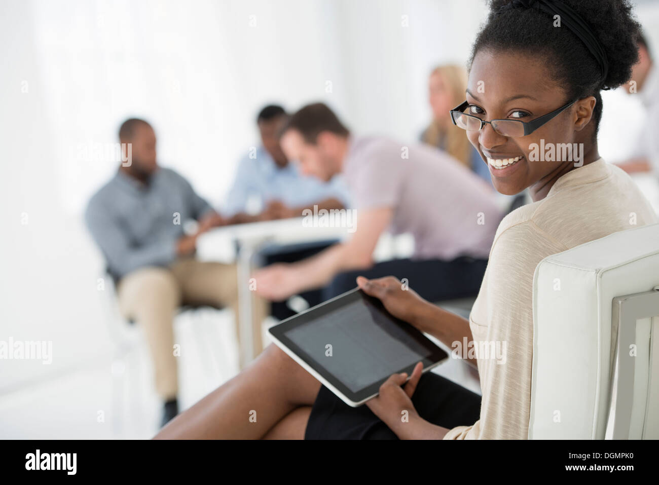 Office interior. Meeting. One person looking over her shoulder and away from the group. Holding a digital tablet. - Stock Image