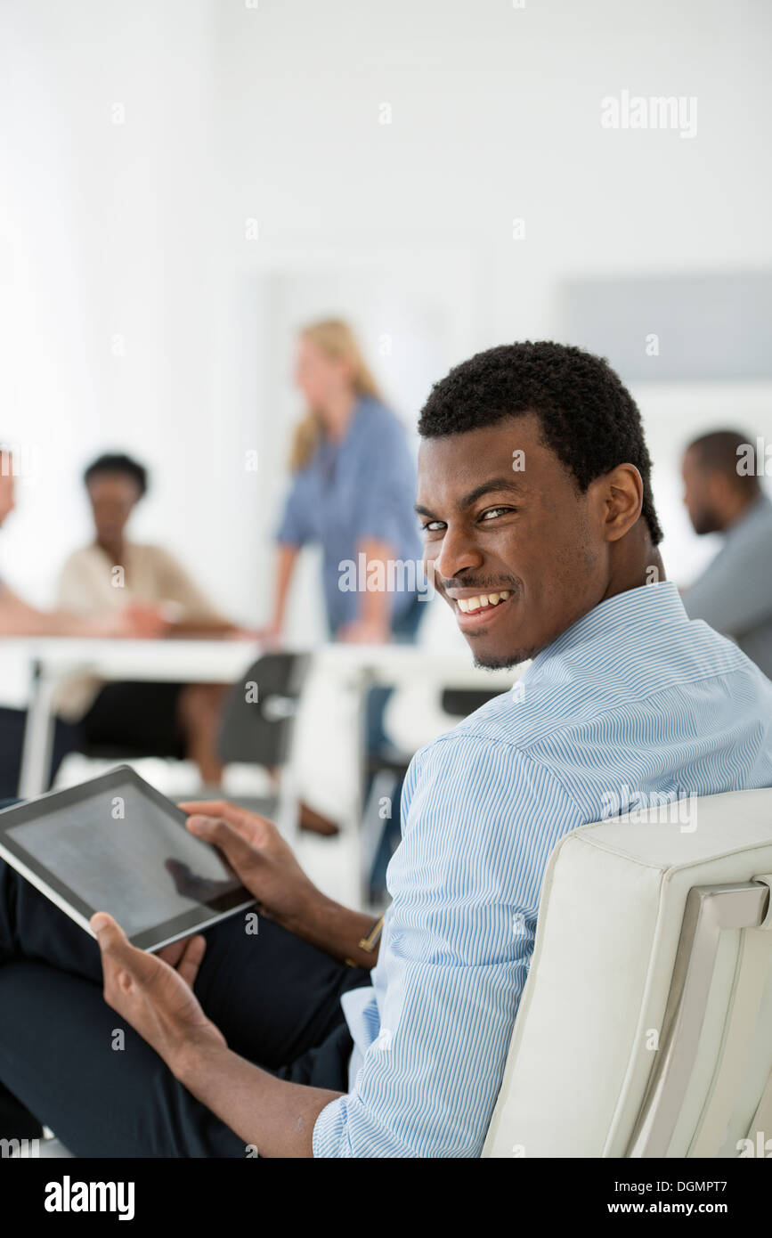 Office interior. Meeting. One person looking over his shoulder and away from the group. Holding a digital tablet. - Stock Image