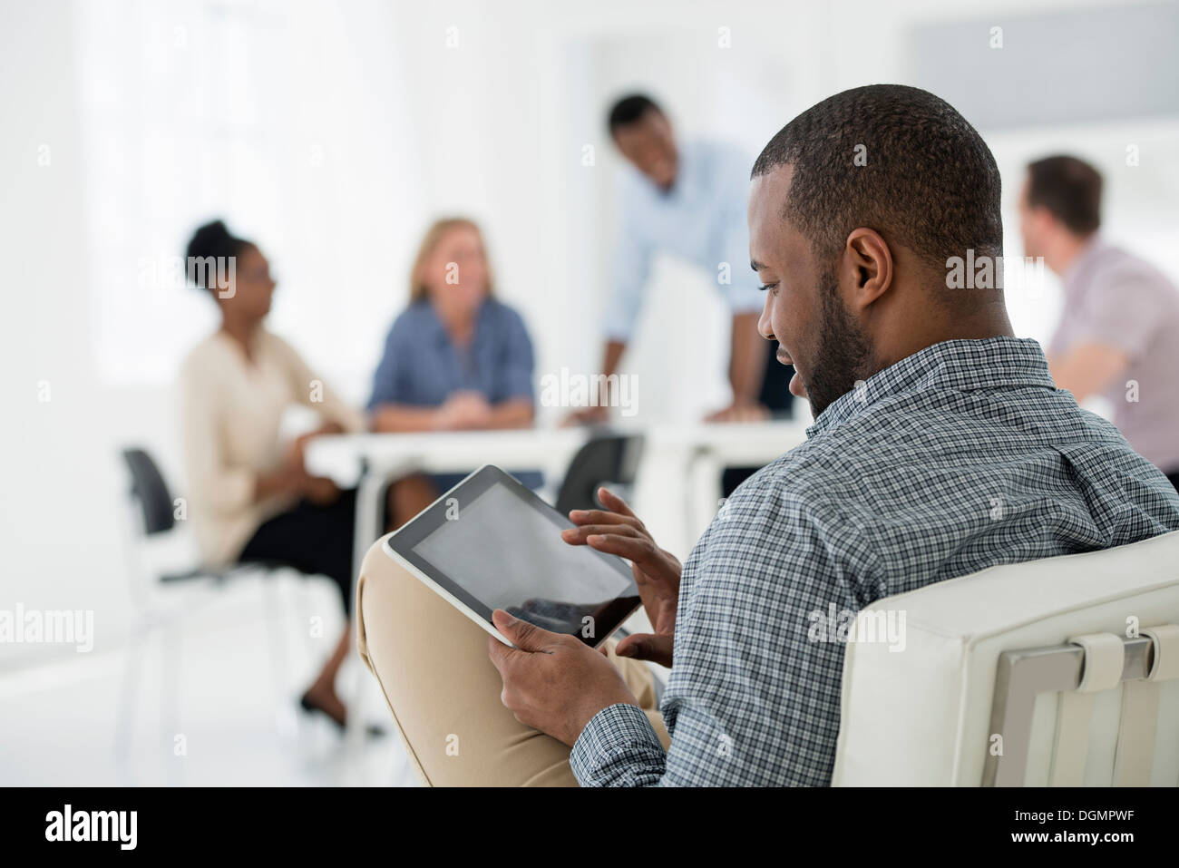 Office interior. Meeting. One person seated separately, using a tablet computer. Holding a digital tablet. - Stock Image