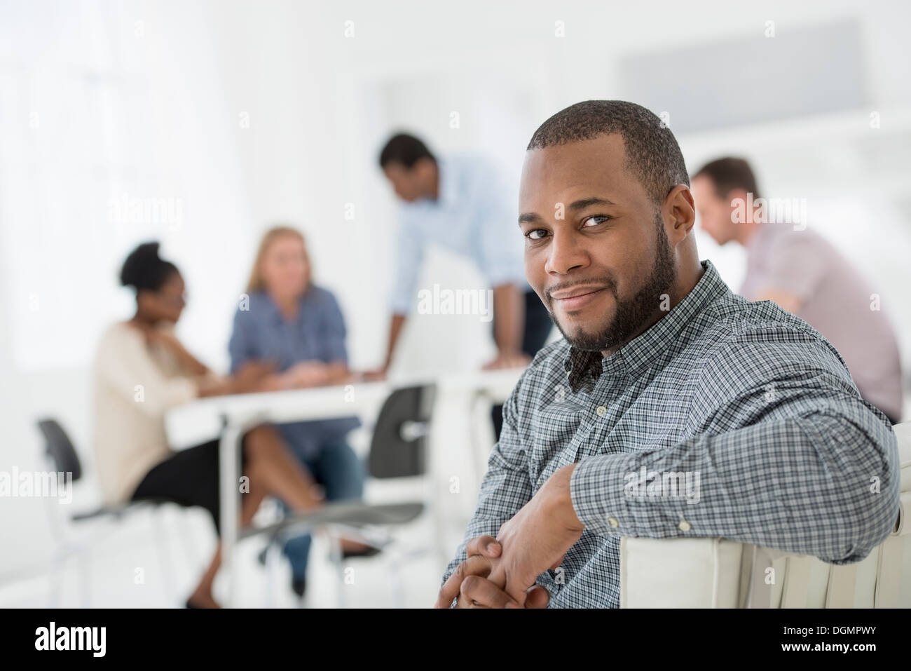 Office interior. Meeting. One person looking over her shoulder and away from the group. - Stock Image