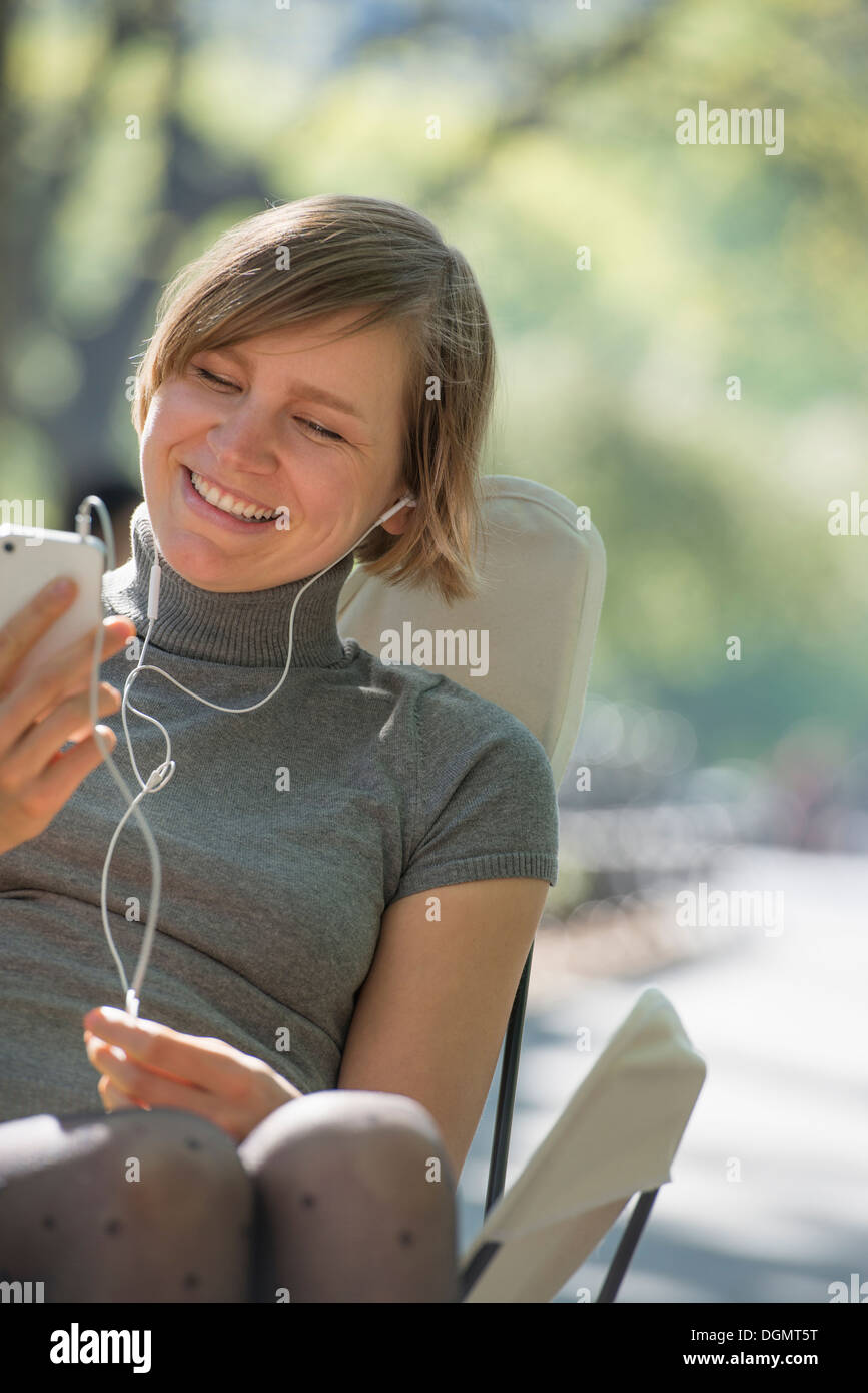 City life. A woman sitting in a camping chair in the park, listening to music wearing headphones. - Stock Image