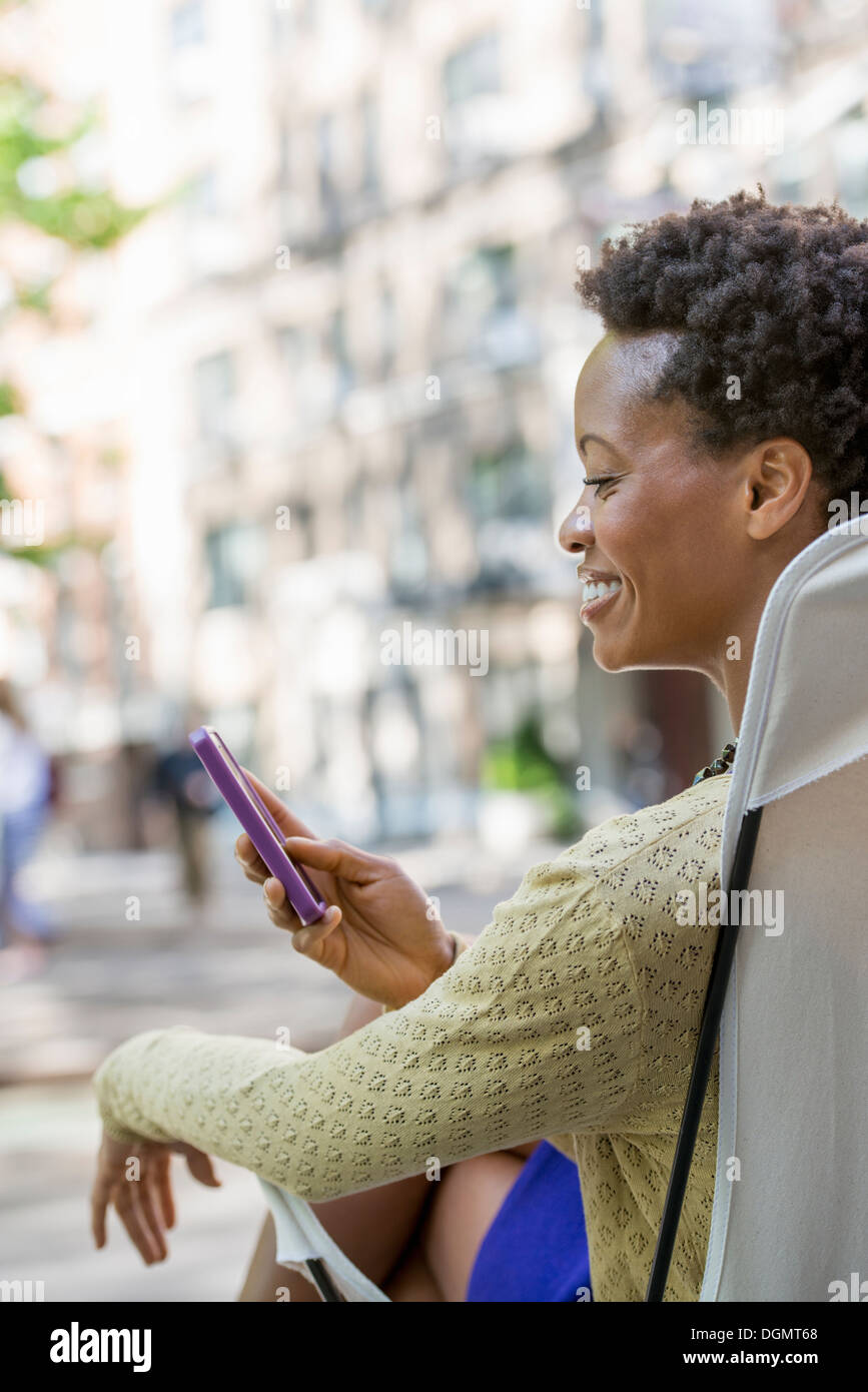 City life. A woman sitting in a camping chair in a city park, checking her cell phone. Stock Photo