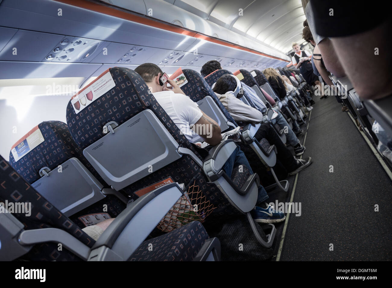Onboard an EasyJet flight, bound for Spain, showing the flight attendant walking the aisle. - Stock Image