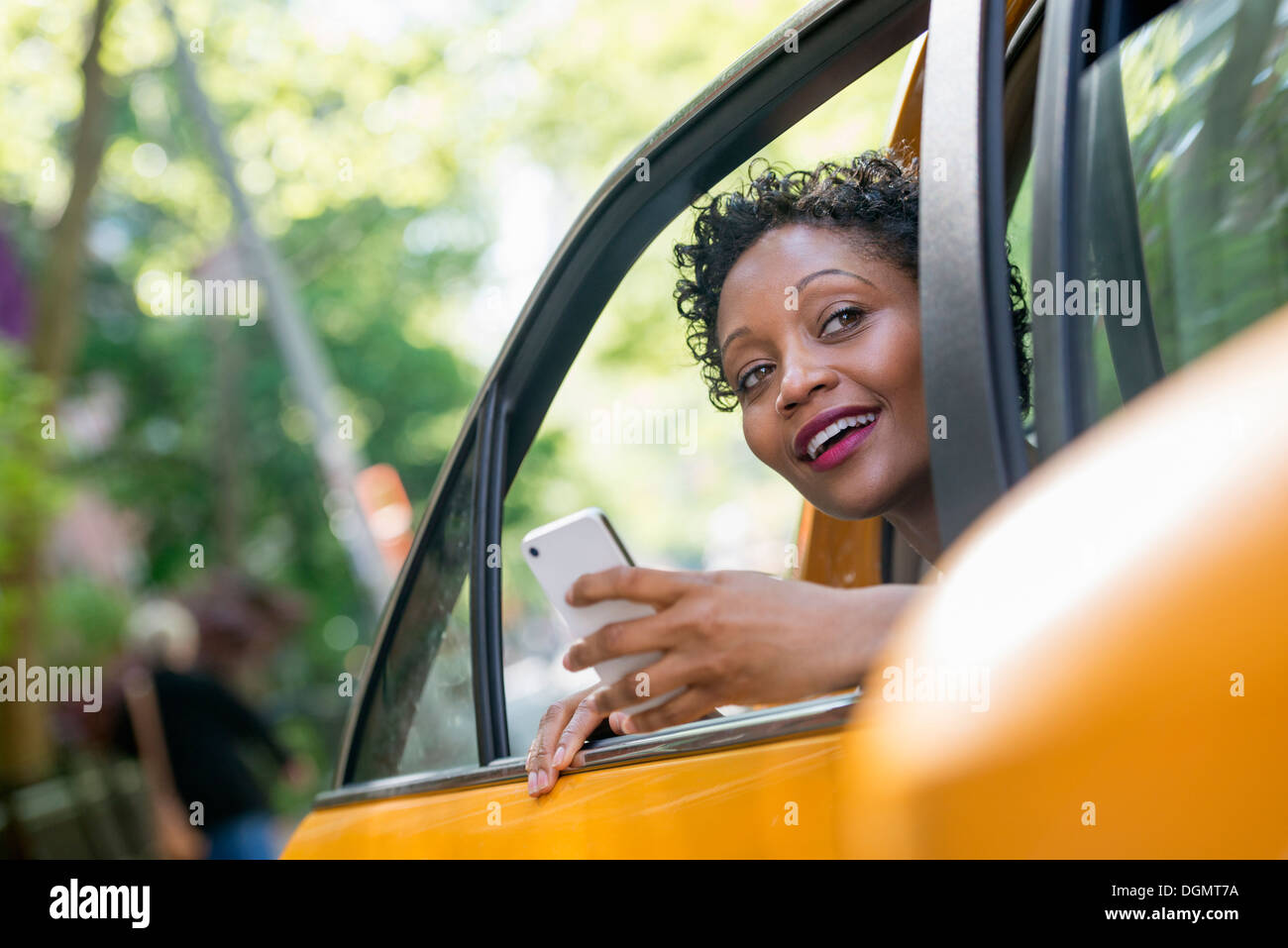 A woman sitting in the rear passenger seat of a yellow cab, checking her phone. - Stock Image