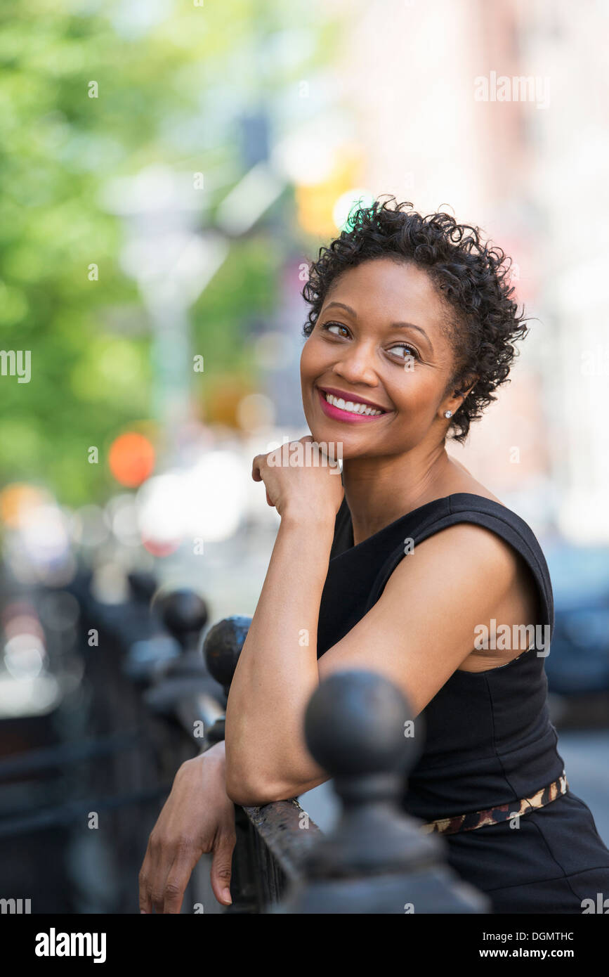 People on the move. A woman in a black dress on a city street. - Stock Image
