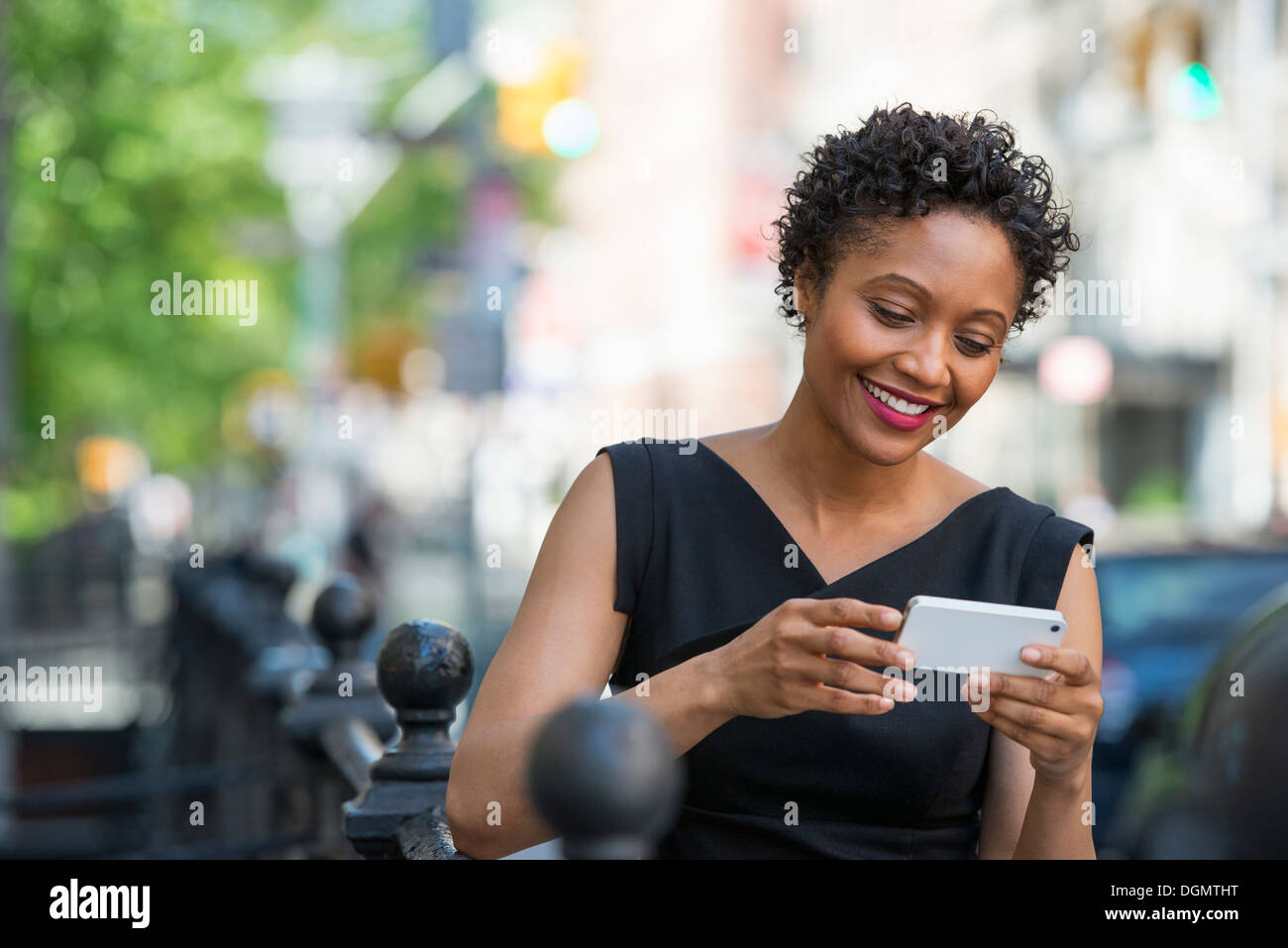 People on the move. A woman in a black dress on a city street, checking her phone. - Stock Image