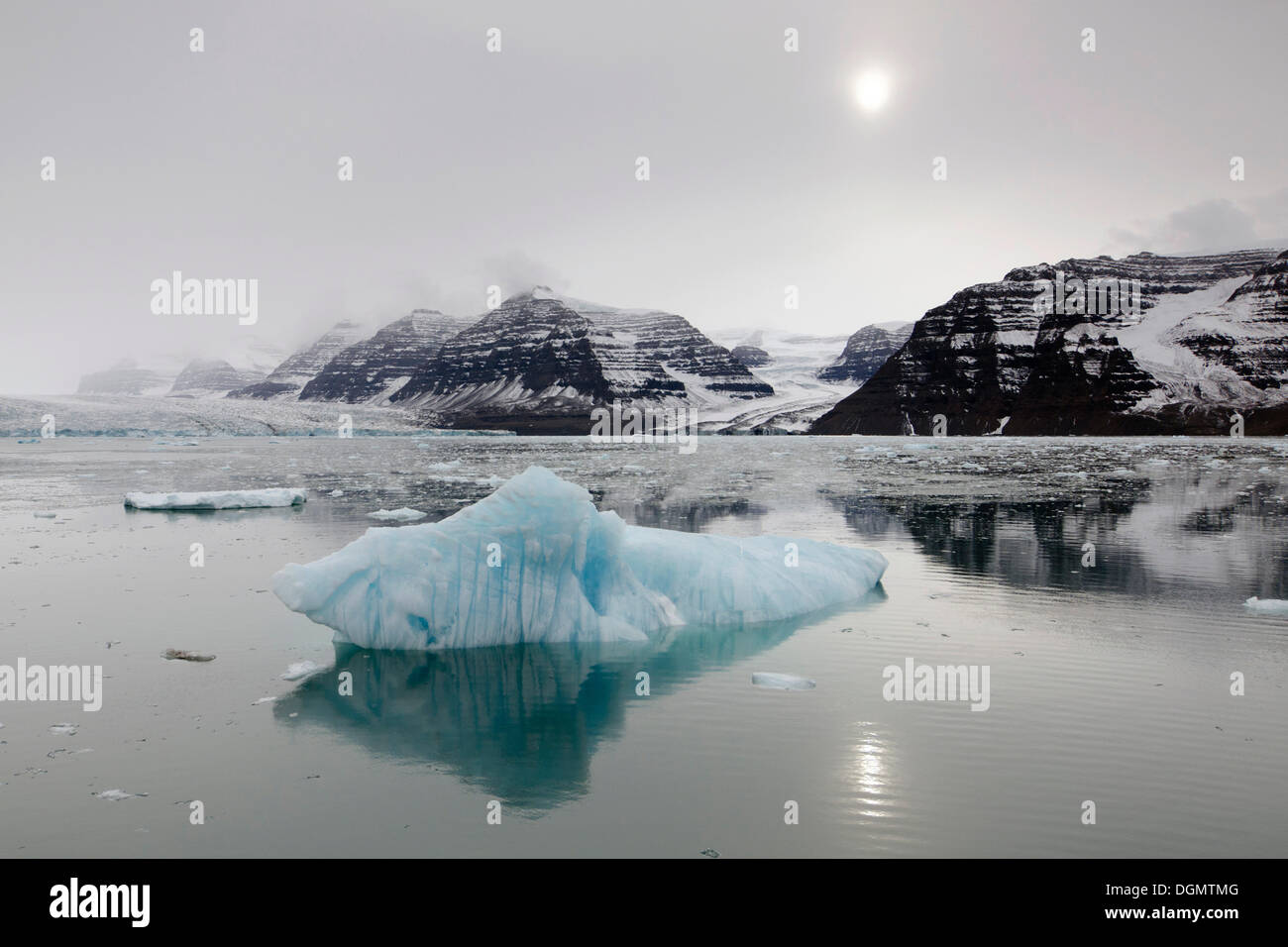 Reflection of icebergs, mountain scenery and the sun on an overcast day, Vikingebugt, Scoresbysund, Sermersooq, Greenland - Stock Image