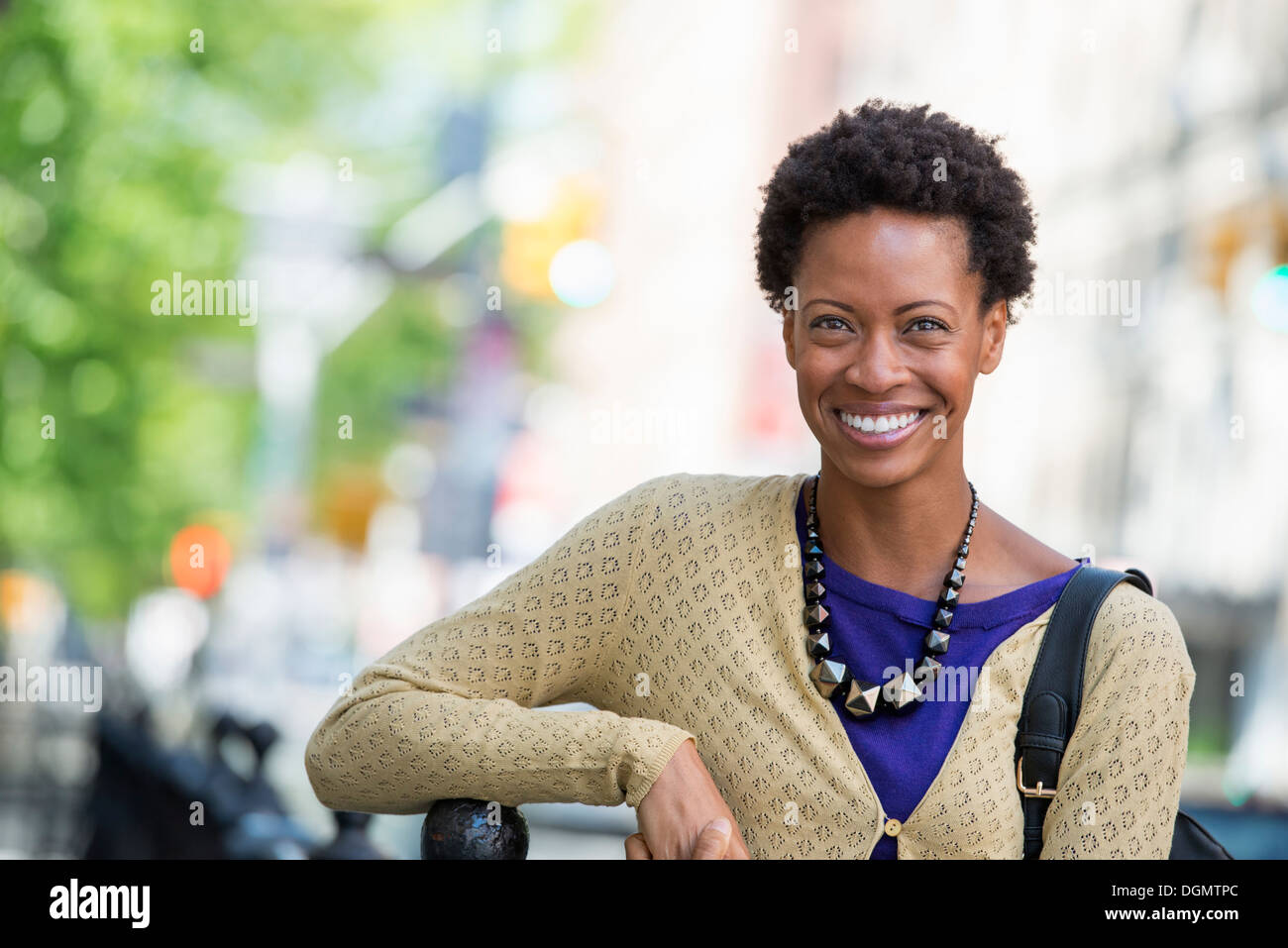 City. A woman in a purple dress, on the city street. - Stock Image